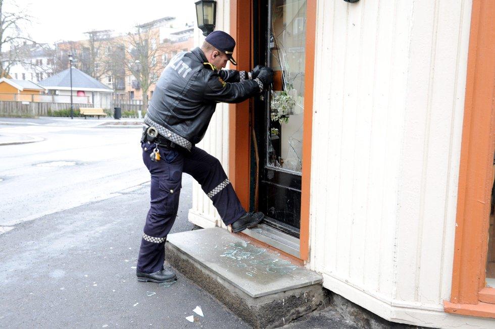 Politibetjent Tom Richard Skuggedal undersøker skadene på inngangsdøra til Sandefjord frisør i Torggata 16. FOTO: PER LANGEVEI
