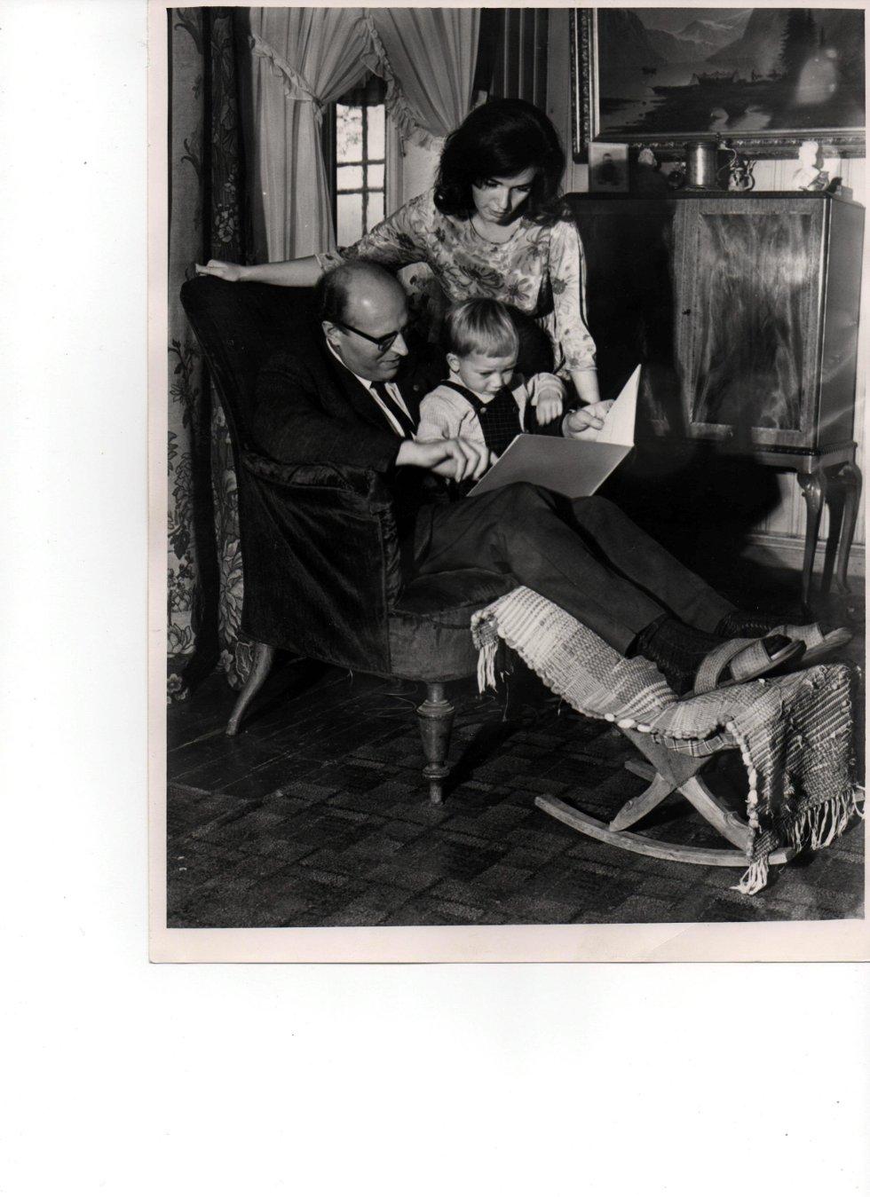 Sønnen til Wilhelm Røren i Asbjørnsens «godstol». Kari Røren, hans datter, bak og på fanget sitter Karis sønn, Arne. Stolen er en polstret lenestol med smidd stamme og sete med fjær, trekk av rød fløyel og dreide ben. Eier: Norsk Folkemuseum. Foto: utlånt av Kari Røren