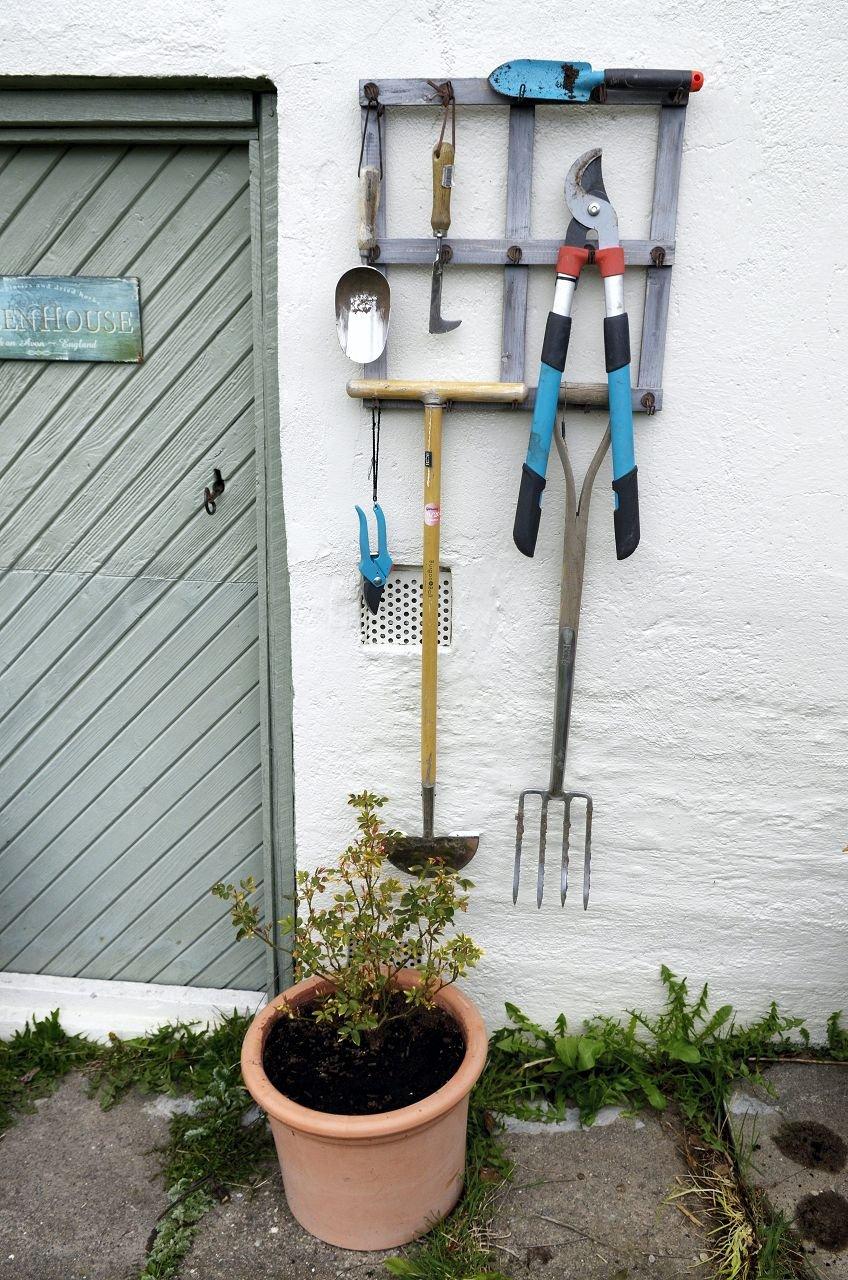 NYTTIG REDSKAP: Hanne har et stativ på veggen med hageredskap hun ofte bruker.