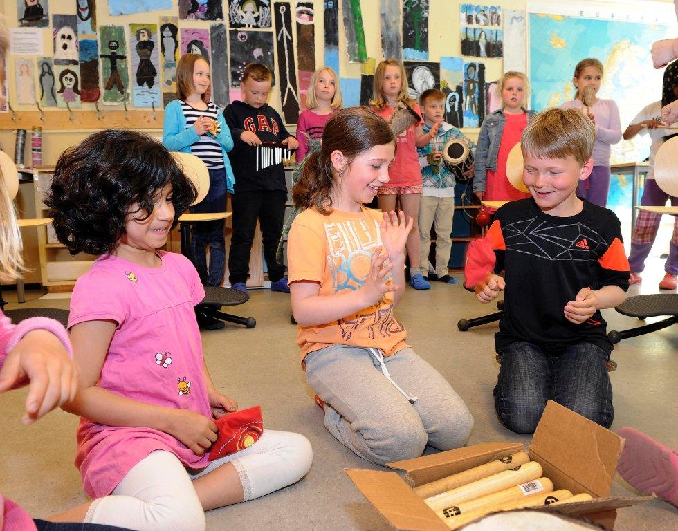 En gruppe 3.-klassinger ved Gokstad skole sitter konsentrert over et pappbrett, mens Elin Hoffart fra Kulturskolen lager rare lyder.      – Bingo! Tre av barna stråler fornøyd.      De spiller rytmebingo.      Tana Dashty Shwani (til venstre), Emilia Pumarino og Erik Hynne.
