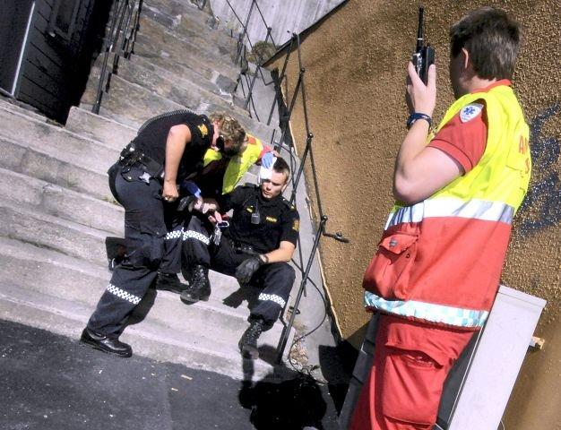 En politibetjent i Arendal får medisinsk bistand etter at 22-åringen har slått ham i hodet med en planke.