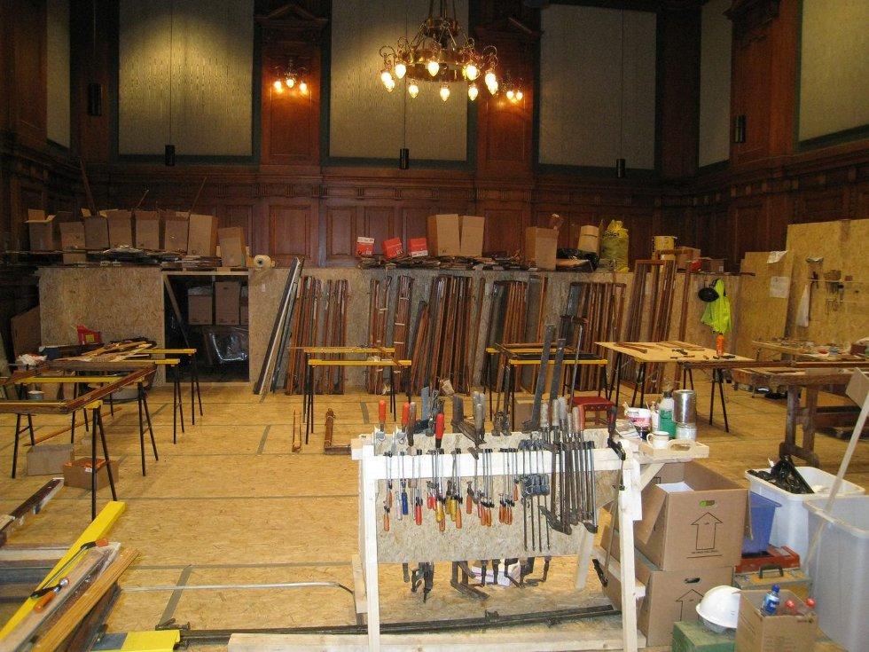 GJENOPPBYGGING: For å få fortgang i arbeidene, satte håndverkene opp et provisorisk snekkerverksted i den åtte meter høye møtesalen. FOTO: PRIVAT