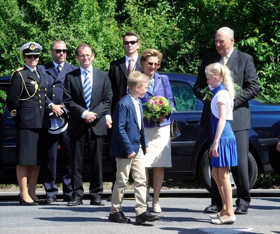 To barn hilser på kongen og dronningen i Andebu sentrum. I bakgrunn står Fylkesmann Erling Lae.