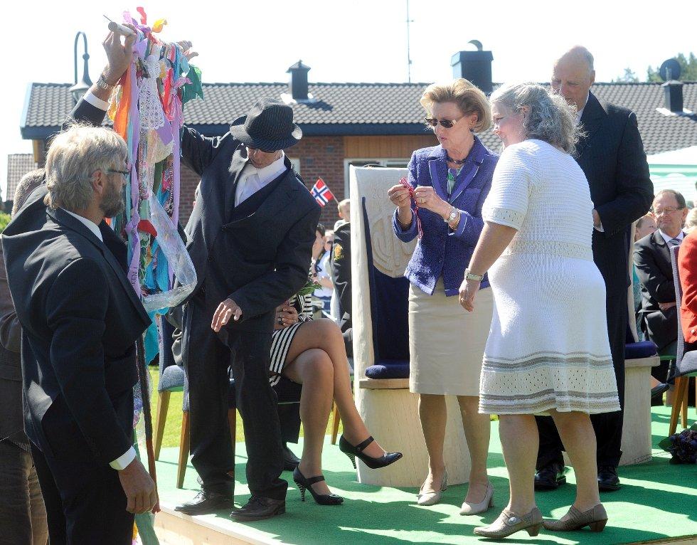 Dronningen knyter et sølvkors på fellesskapsteppet på Signo i Andebu. Teppet skal henges i Thomas-kirken. Foran dronningen står arbeidsleder i Signo, Bente Aanerud.