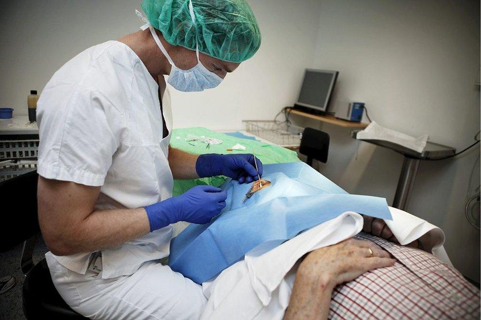 INJEKSJON: Konstituert overlege Erlend Sommer Landsend gir denne eldre pasienten en injeksjon med et kjemisk stoff rett i øyet. En av 10 personer over 60 år lider av AMD, bedre kjent som forkalkinger i øyet. Gruppen er høyt prioritert.Foto: Christian Roth Christensen