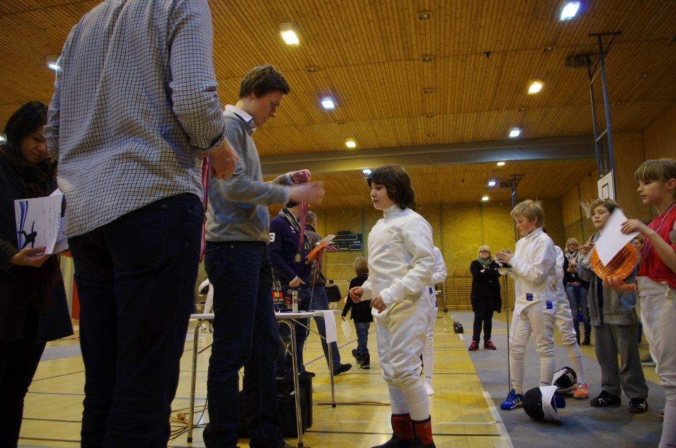 Sølvmedaljist Bartosz Piasecki fra Bygdø Fekteklubb deler ut medaljer til alle i klassen for de under 11 år.