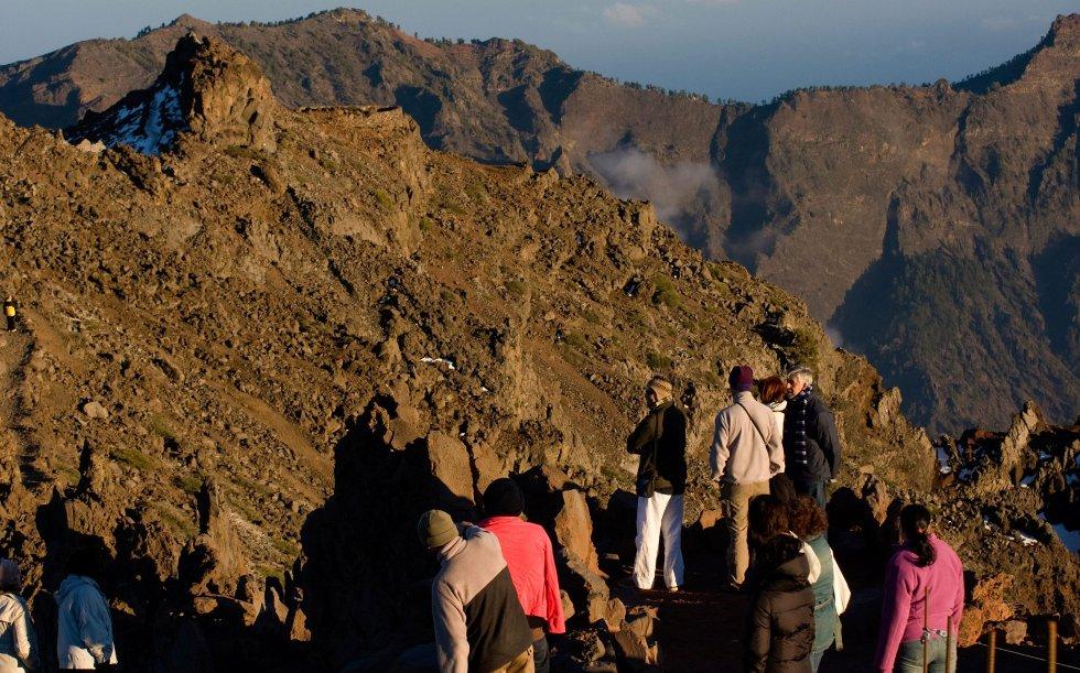 I brennende sol balanserer turistene på kanten av vulkanen Cumbre Vieja på øya La Palma.