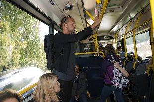 Busspassasjerene følger nøye med når Harald Rosenløv Eeg leser fra boken sin «Yatzy».
