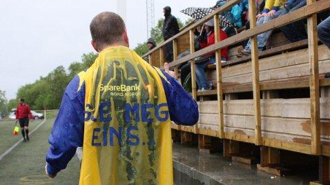 Speaker Jan Ove Styve stilte i nylaget og spesialsydd «Gje meg ein S!»-kappe til SIL-fotballherrenes kamp mot Bodø/Glimt 2, og oppildnet folk på tribunen. Foto: Leif Steinholt
