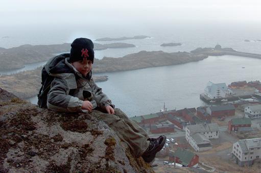 """Joakim-Tark Paulsen på tur opp """"Kattberget"""", med utsikt over endel av ytre Stamsund og Skjærbrygga i bakgrunnen."""