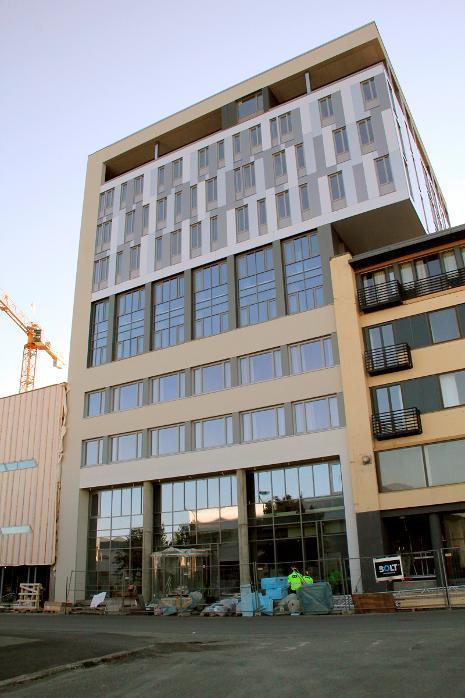 REV STILLASET: Onsdag framsto endelig den imponerende fasaden på det nye hotellbygget i Sandnessjøen, da stillaset ble revet. Den nye resepsjonsinngangen ses på gateplan. Oppover i etasjene ser vi allerede gardiner i vinduene, som tilsier at bygget snart er klart til bruk, også på innsiden. foto: morten hofstad