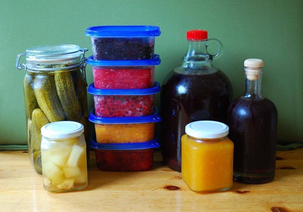 ommersmaker: Sylteagurker, syltet gresskar med ingefær (foran), frysetøy av blåbær (øverst), bringebær, tyttebær, multer, jordbær (nederst), blandingssaft av solbær og rips og aprikosmarmelade foran til høyre.