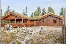 Åmot: Stor hytte med god takhøyde og store rom. Lekker peisinnsat innmurt i naturstein. Flott tomt med utsikt.