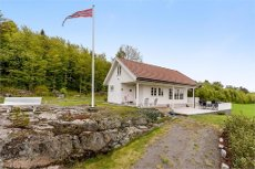 Landsted/hytte beliggende i naturskjønneomgivelser rett ved grensen til Stokke 2 soverom - åpen stue/kjøkkenløsning - innglasset sommerstue med peis.