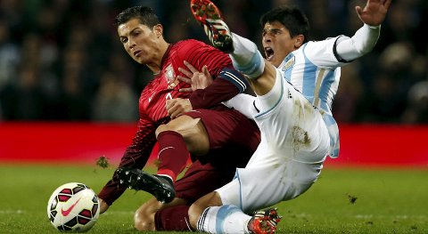 Argentina's Facundo Roncaglia (R) challenges Portugal's Cristiano Ronaldo during their international friendly soccer match at Old Trafford in Manchester, northern England November 18, 2014. REUTERS/Phil Noble  (BRITAIN - Tags: SPORT SOCCER)