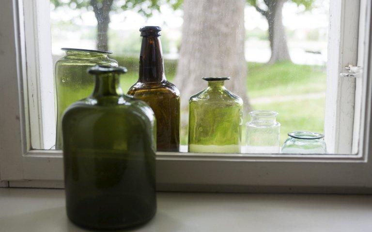Pensjonister: Apotekets gamle medisinflasker nyter pensjonisttilværelsen i Gjones stuevindu.