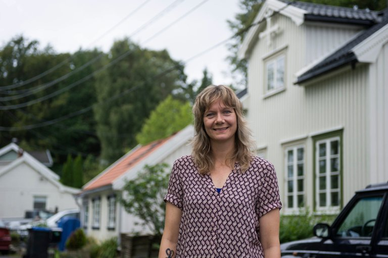 SKILLER SEG UT: Huset til høyre bak Christine Lande skiller seg ut ettersom det er bygget av hel tømmer.  - Kanskje var det en formann som bygde huset.