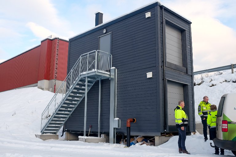 Det nye renseanlegget står inne i denne blå bygningen. Bassenget som samler opp sigevann står i det røde bygget i bakgrunnen.
