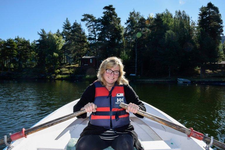 Vivi Rian lærte tidlig å traktere robåt. Her er hun på vei mot land med hytta på Amundøya bak til venstre.