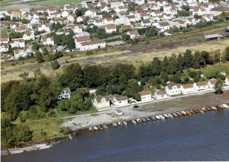 ARBEIDERHUS: Arbeidere ved Lisleby bruk bodde i husrekken nederst mot vannet. Christine Landes hus er nummer fem fra venstre. Bildet er tatt i 1963.