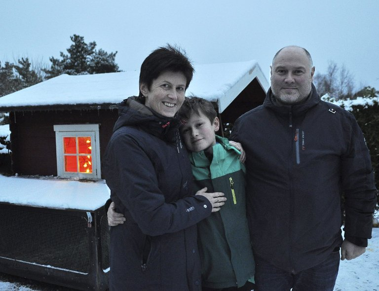 Fugleeiere: Mor Kari, Marius og far Carl Aage foran den omgjorte lekestuen. Marius har selvfølgelig hengt opp julelys til vaktlene.