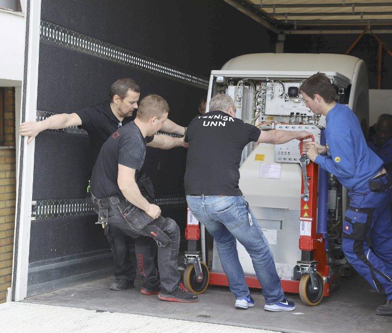 TUNGE TAK: Maskinen veier rundt tre tonn, men den havnet der den skulle etter solid samarbeid av flere parter.