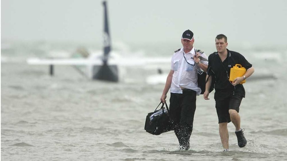 Pilot Steve Bolle, left, and an unidentified passenger walk from the water after the safe landing of a Piper Chieftain, seen in rear, in shallow waters off the northern city of Darwin, Australia, Friday, Feb. 6, 2009. The plane came to rest on a sand bank in about two feet of water at low tide after experiencing engine trouble shortly after takeoff. All six people were able to wade the 200 yards (meters) to the beach. (AP Photo/Sydney Morning Herald, Glenn Campbell)