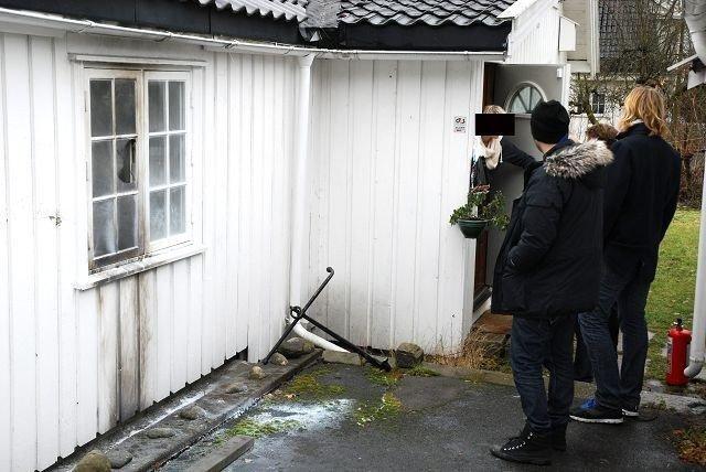 Det tok fyr i veggen og ruten sprang i bolighuset. I bakgrunnen er sønnen i huset i samtale med journalister.
