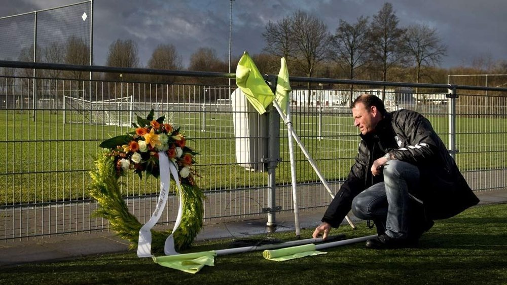 A picture taken on December 9, 2012 shows a man putting down corner flags at the memorial site for linesman Richard Nieuwenhuizen at the clubhouse of Dutch football club SC Buitenboys in Almere. Nieuwenhuizen collapsed and fell into a coma after he was attacked by three teenagers at the end of a junior club football match on December 2, 2012. The verdict in case of seven Dutch teens and a father accused of kicking to death an amateur football linesman is expected on June 17, 2013