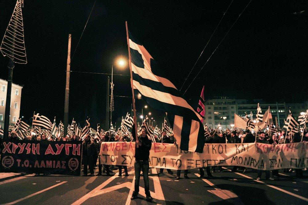 HEVER FLAGET: En tilhenger av det høyreekstreme greske partiet Gyllent Daggry hever det greske flagget under en demonstrasjon utenfor parlamentet i november i fjor da man protesterte mot fengslingen av partimedlemmer etter drapet på antifascisten og rapperen Pavlos Fyssas.