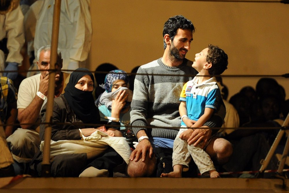 STOR PÅGANG: Italia opplever en enorm tilstrømming av flyktninger og asylsøkere. Bildet viser flyktninger på vei inn til havn på Sicilia etter en redningsaksjon utenfor kysten.