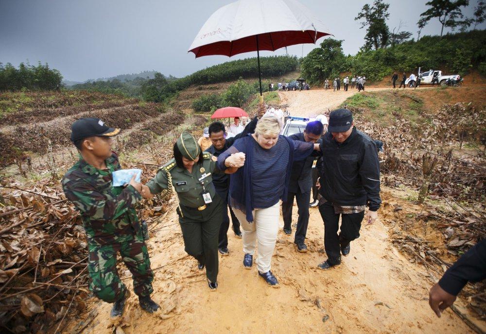 I GJØRMA: Statsminister Erna Solberg på vei til Orang Rimba Bujang Tampui stammen i regnskogen på Sumatra onsdag. Det har regnet kraftig og veiene er dels ubrukelige. Derfor måtte Solberg gå de siste 800 meterne i gjørma.