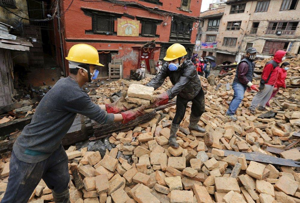 RYDDER: Bildet viser frivillere som forsøker å rydde i sammenraste byer. Fremdeles er mange savnet etter jordskjelvet. Søndag ble tre personer funnet i live.