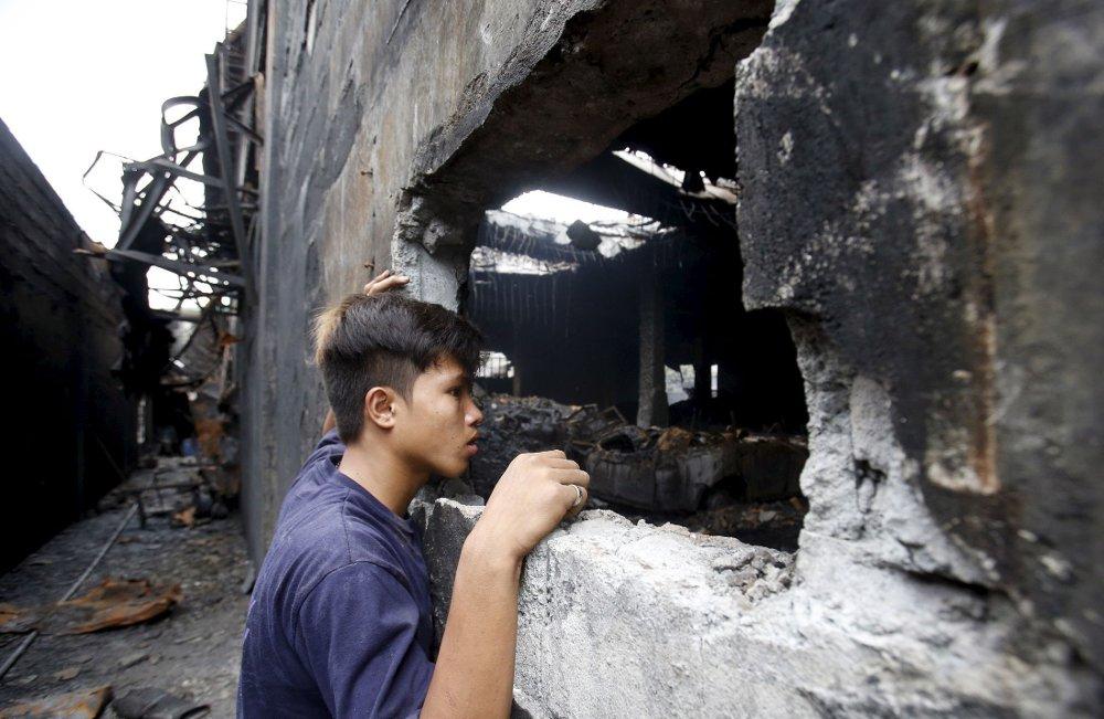 En fabrikkarbeider som overlevde brannen i skofabrikken i Manila, ser inn i brannruinen der mange av hans kolleger omkom.