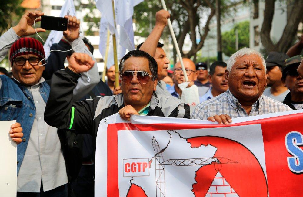 Fagforeningsmedlemmer protesterer mot Perus korrupsjonsanklagede ekspresident Alan Garcia, som i november søkte asyl i Uruguas ambassade i Lima. Foto: AP / NTB scanpix