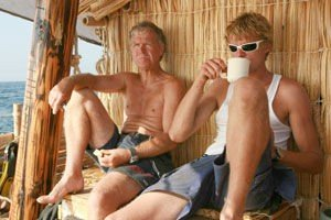 Flåten seiler på egen hånd, og Bjarne og Olav spiser i hytteveggen.