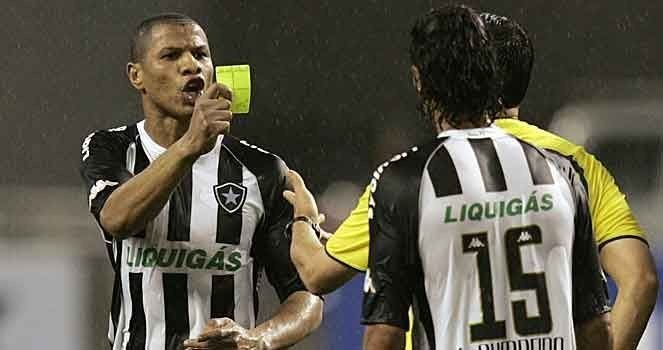 Andre Luiz of Brazil's Botafogo takes the yellow card from the referee during their Copa Sudamericana soccer match against Argentina's Estudiantes