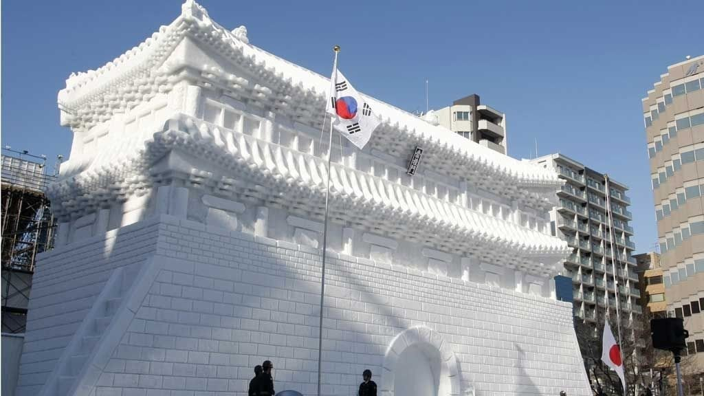 Japan's self-defense army soldiers raise South Korea's national flag in front of a snow sculpture in the shape of South Korea's 'Namdaemun', which was badly damaged by fire in 2008, at a rehearsal for the opening of the 60th Sapporo snow festival, northern island of Japan, February 4, 2009. About 270 snow and ice sculptures are exhibited in the one of Japan's famous winter events which goes on from Feb 5 to 11. REUTERS/Kim Kyung-Hoon (JAPAN)