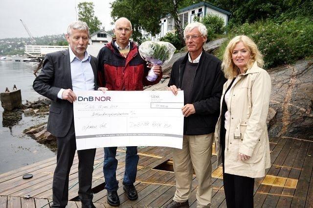 Finn Erhard Johannesen og Anders Wahl i Ljan Vel (i midten) fikk 125.000 av Jann Simonen og Lis Engell i DNB NOR, Sparebankstiftelsen.