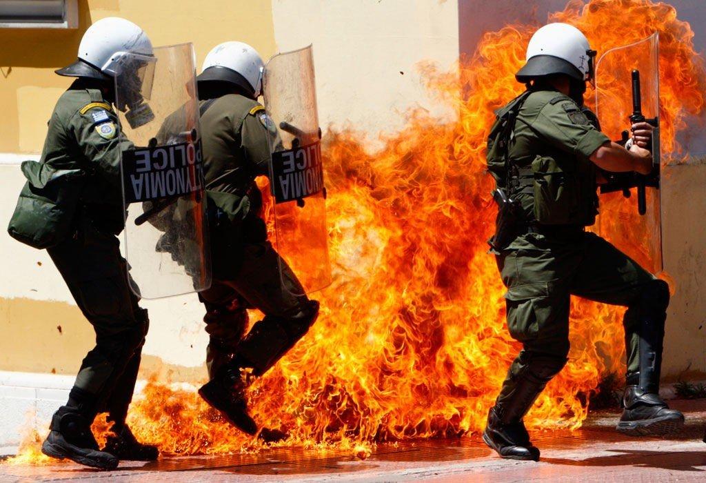 ARBEIDERNES DAG I HELLAS: Opprørspoliti sliter med å komme seg bort fra en bensinbombe under demonstrasjonene i Aten 1. mai.