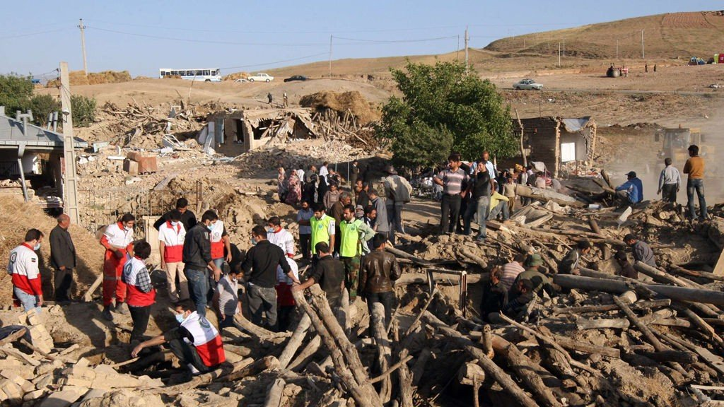 Iranian residents and rescue workers search for survivors in the rubble of a house in the village Baje-Baj, near the town of Varzaqan, on August 12, 2012, after twin earthquakes hit northwestern Iran on August 11. Iran wrapped up rescue operations in hundreds of villages flattened by twin earthquakes the day before in its northwest, as officials gave a new toll of 227 dead and 1,380 injured in the disaster. AFP PHOTO/ATTA KENARE