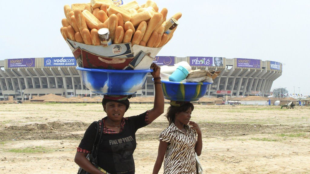 """A woman carries bread past the Martyrs Stadium, one of the venues for the 14th annual Francophonie summit, in Kinshasa October 12, 2012. France's President Francois Hollande said on the eve of his first state visit to Africa that he wanted to open a new chapter in France's relations with former colonies and would denounce a period of colonisation as a historical """"mistake""""."""
