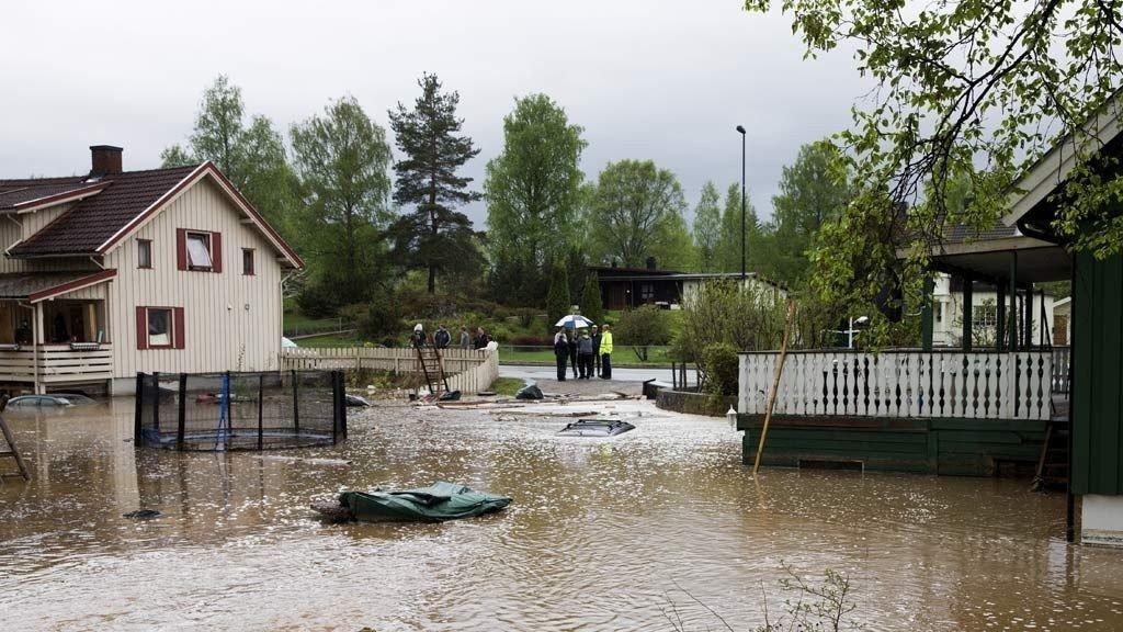 Flom på Vallset syd for Hamar. Der veien ble stengt for gjennomfartstrafikk. To hus der hagene og innkjørsel var dekt med vann. Noe som skjedde i løpet av en halvtime tidlig idag. Foto: Berit Roald / NTB scanpix