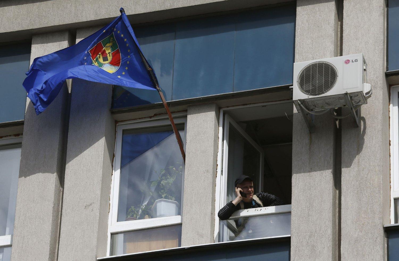 HOLDER STAND: De prorussiske separatistene i Øst-Ukraina vil ikke gi seg. Bildet viser en av demonstrantene i et vindu på en okkupert bygning i Luhansk fredag. Bygningen tilhører den ukrainske sikkerhetsstyrken SBU.