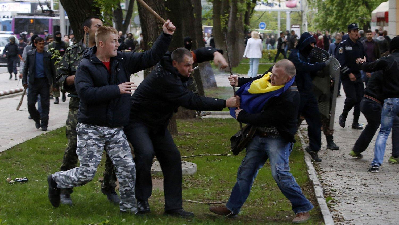 FLERE SKADD: Pro-russiske demonstranter angriper en pro-ukrainsk demonstrant under en demonstrasjon i Donetsk 28. april.