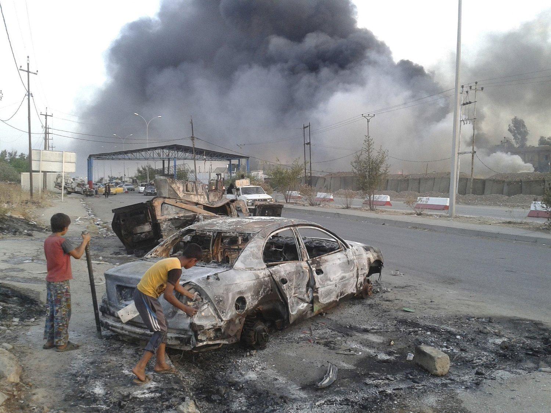 Irakiske barn ved en utbrent bil i Mosul, som tirsdag ble erobret av den ytterliggående opprørsgruppen ISIL. Nå er det byen Tikrit, den avdøde diktatoren Saddam Husseins hjemby, som inntas av militante islamister.