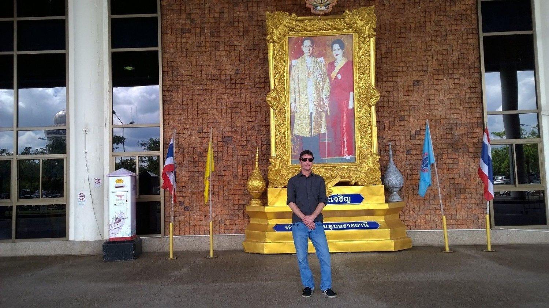 Nettavisens Asia-korrespondent Stig Martin Solberg foran et maleri av Thailands kongepar på flyplassen i Ubon Ratchatani.