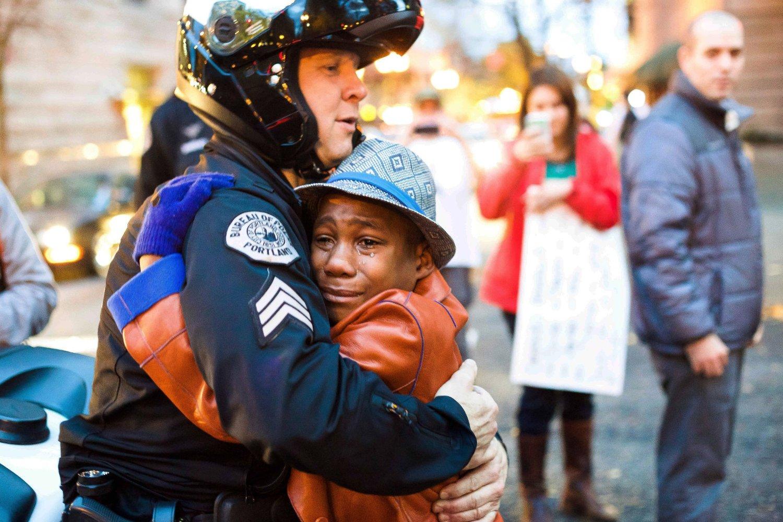 GRATIS KLEMMER: Devonte Hart (12) fra Portland, Oregon mener fortsatt at det er kjærlighet som bør gjelde etter dødsskuddene i Ferguson. Under en demonstrasjon i hjembyen sin hadde han med seg et skilt hvor det sto «Gratis klemmer». Politimannen Bret Barnum så skiltet og gikk frem og spurte gutten om han kunne få en klem. Dette bildet går sin seiersgang verden over.