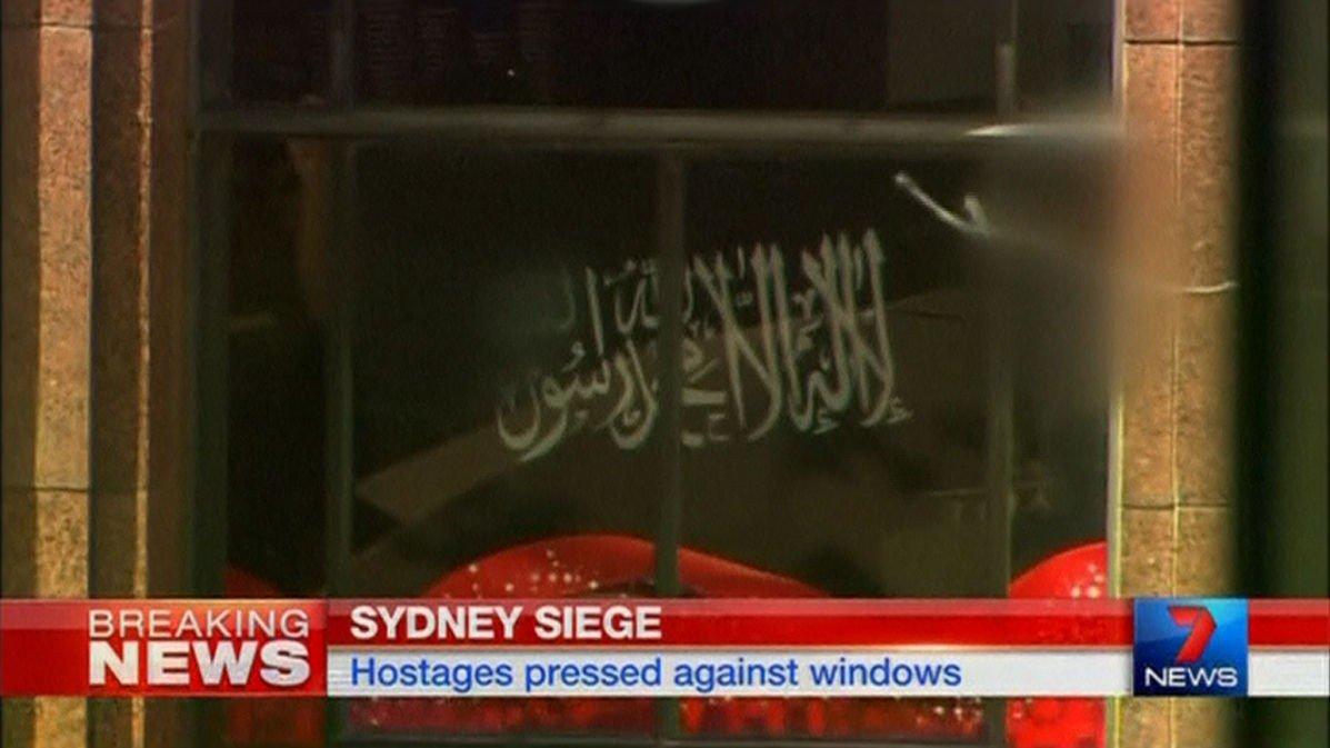 Flere av gislene ble tvunget til å holde opp mot vinduet. Flagget har den muslimske trosbekjennelsen i arabisk skrift, men er ikke det såkalt offisielle flagget til Den islamske staten (IS).