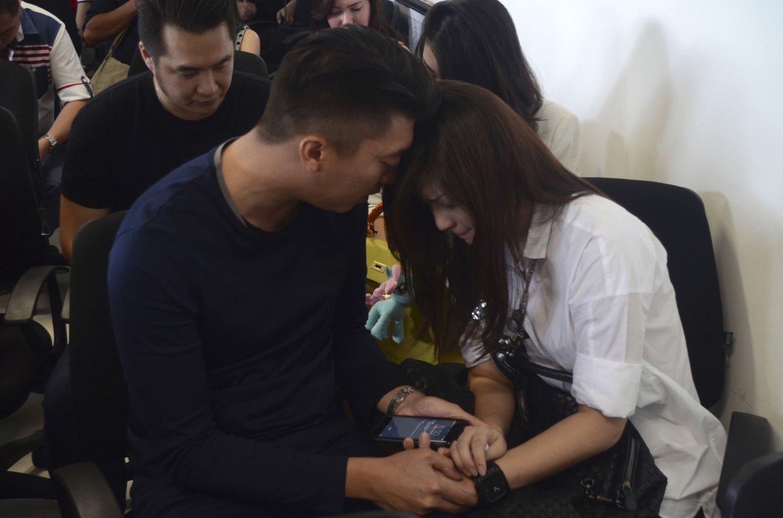 I SORG: Familiemedlemmer til passasjerer om bord på Air Asias fly QZ 8501 venter på å få mer informasjon inne på et krisesenter på Juanda internasjonale flyplass i Surbaya i Øst-Java, Indonesia søndag morgen.